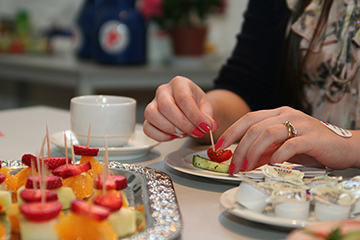 Foto: Ein Tisch mit Obstspießen und anderen Lebensmitteln sowie  ein Teller mit den Händen einer Frau, die isst.