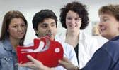 Foto: Eine Kursleiterin zeigt den Kursteilnehmern die oberen Atmungsorgane an einem Modell. Dieses Foto ist gleichzeitig ein Link und führt Sie zu der Unterseite: Erste-Hilfe-Lehrgang.