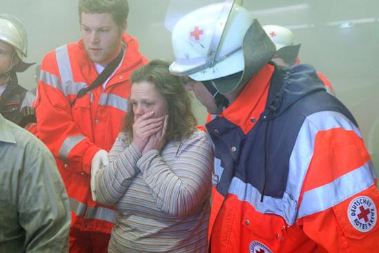Foto: Zwei Helfer kümmern sich um eine Frau, die schockiert an einem Einsatzort steht.