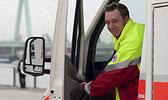 Foto: Ein Rettungssanitäter öffnet lächelnd die Tür eines  Rettungswagens.
