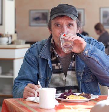Foto: Ein Mann trink aus einem DRK-Glas am Tisch mit einem Teller  Essen.