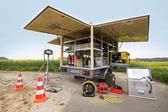 Foto: Ein aufgebauter Technikanhänger an einem blühenden Rapsfeld.